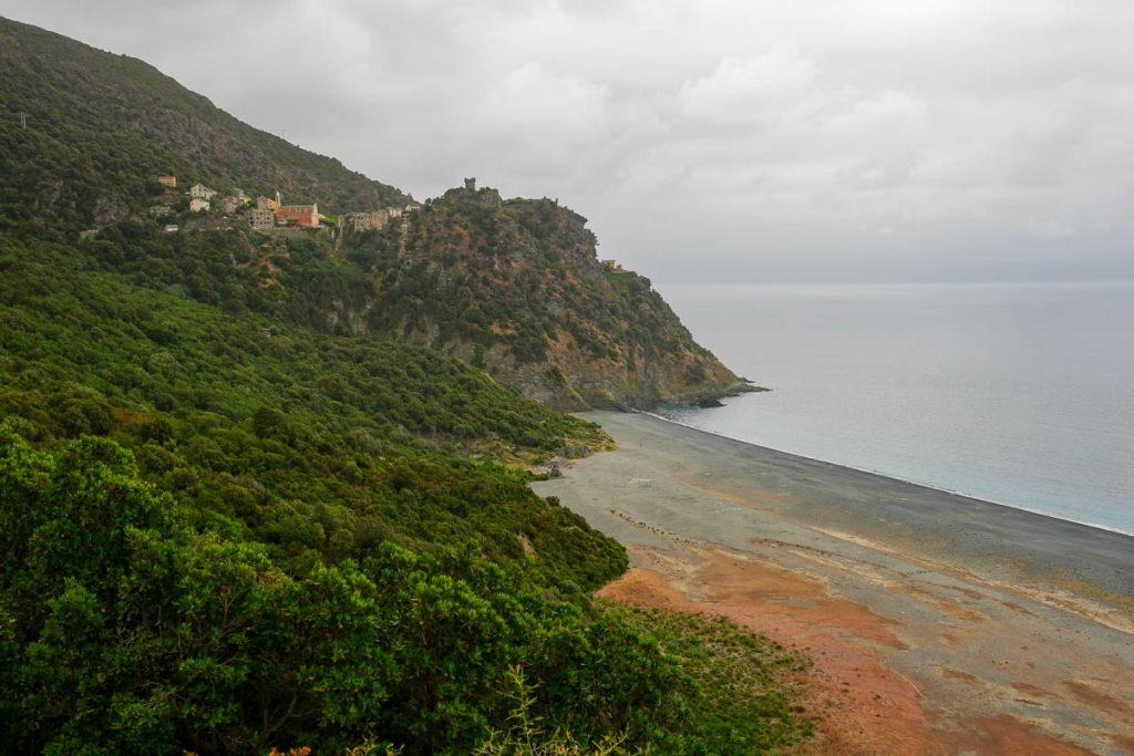 Plage sable noir Nonza et village perché
