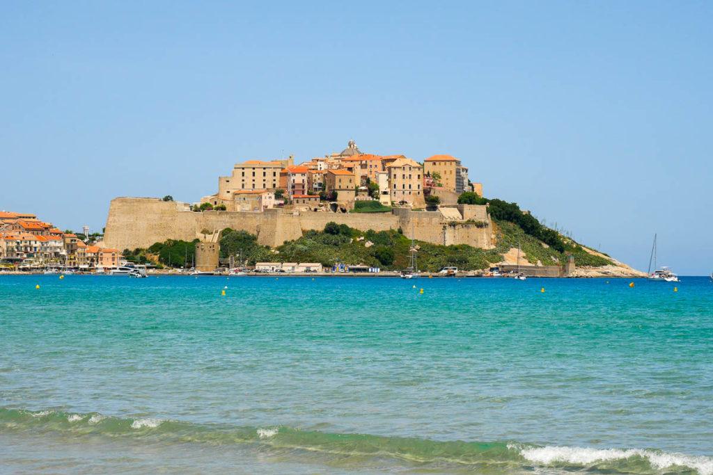 Vue sur la citadelle de Calvi en Corse et les remparts depuis la plage